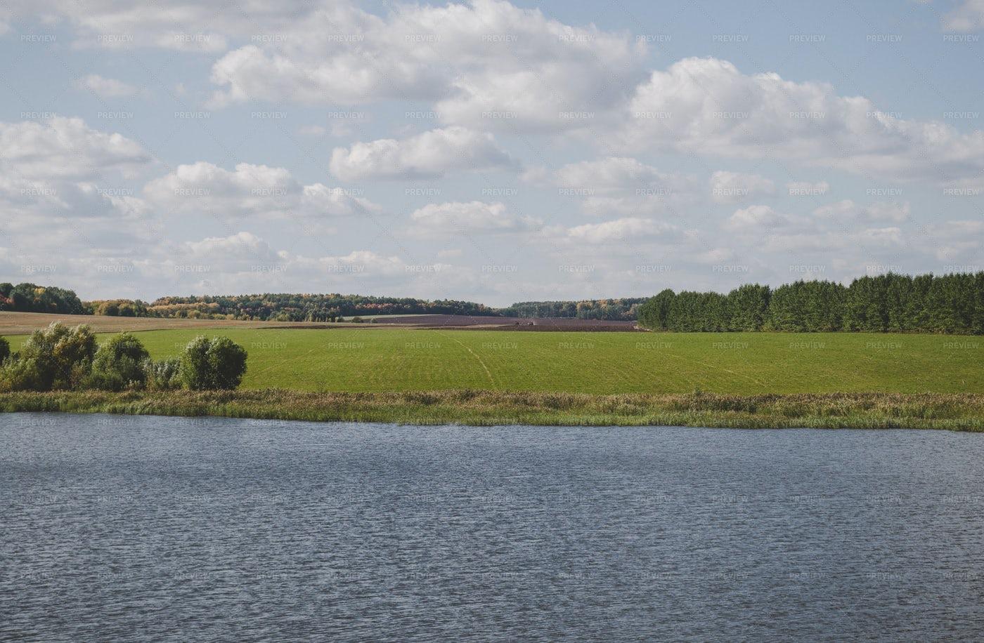 Harvested Farmland Beside A Lake: Stock Photos