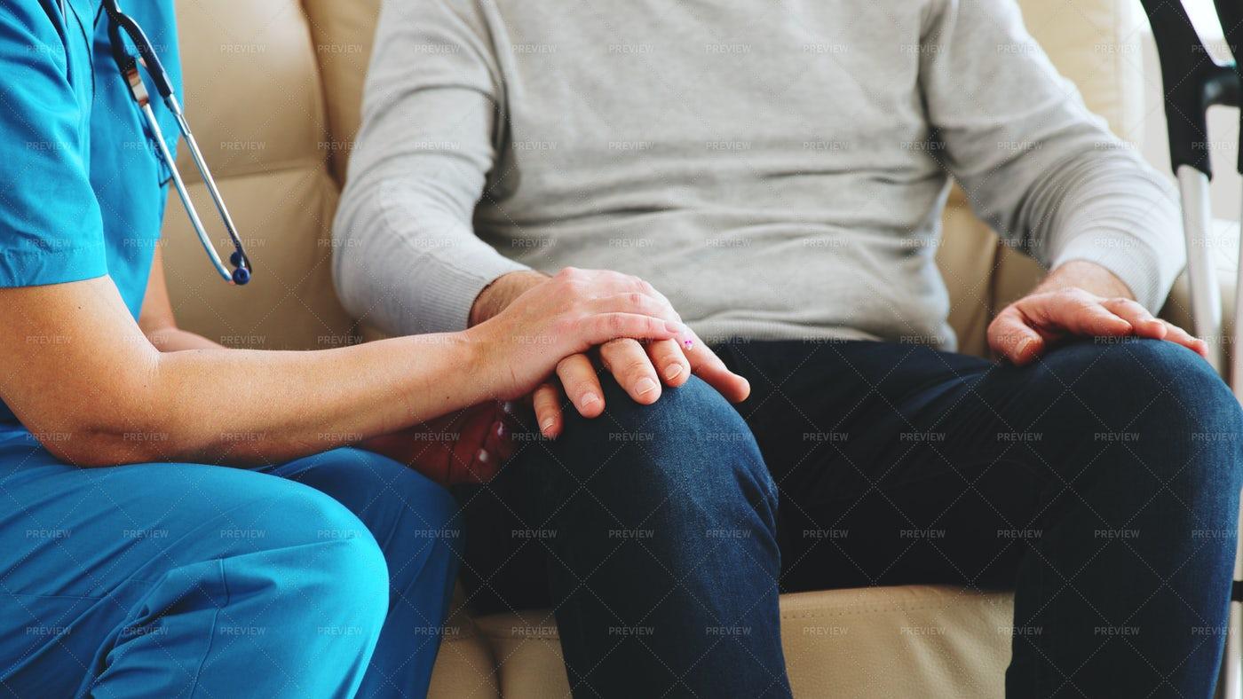 Female Nurse Taking An Old Man's Hand: Stock Photos