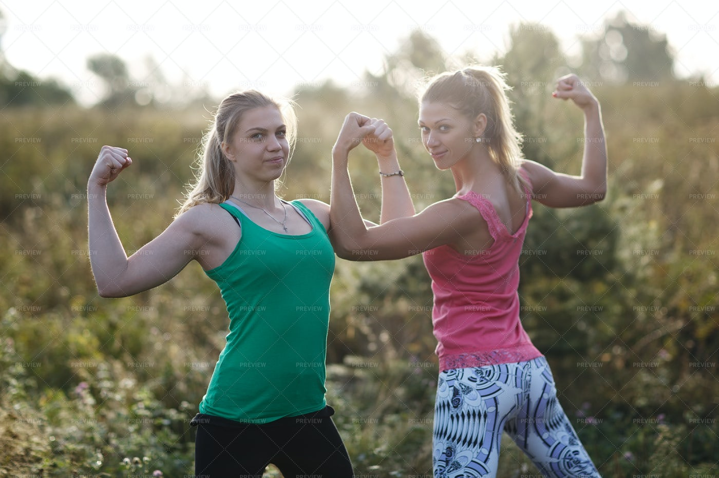 Athletic Girls Flexing Their Arms: Stock Photos