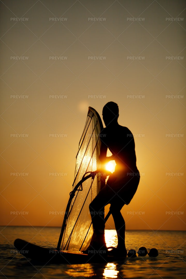 Man Sailboarding At Sunset: Stock Photos