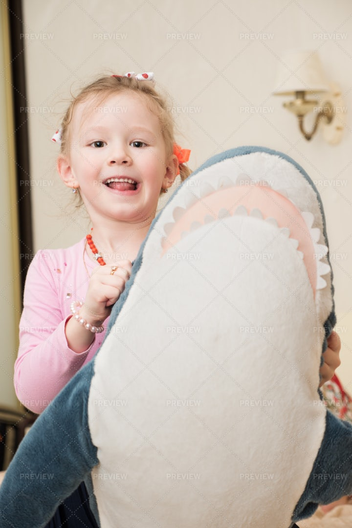 Girl Playing With Shark Toy: Stock Photos