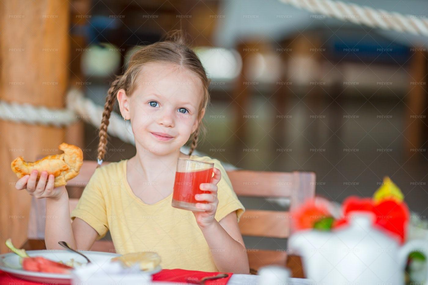 Little Girl Eating On A Restaurant: Stock Photos