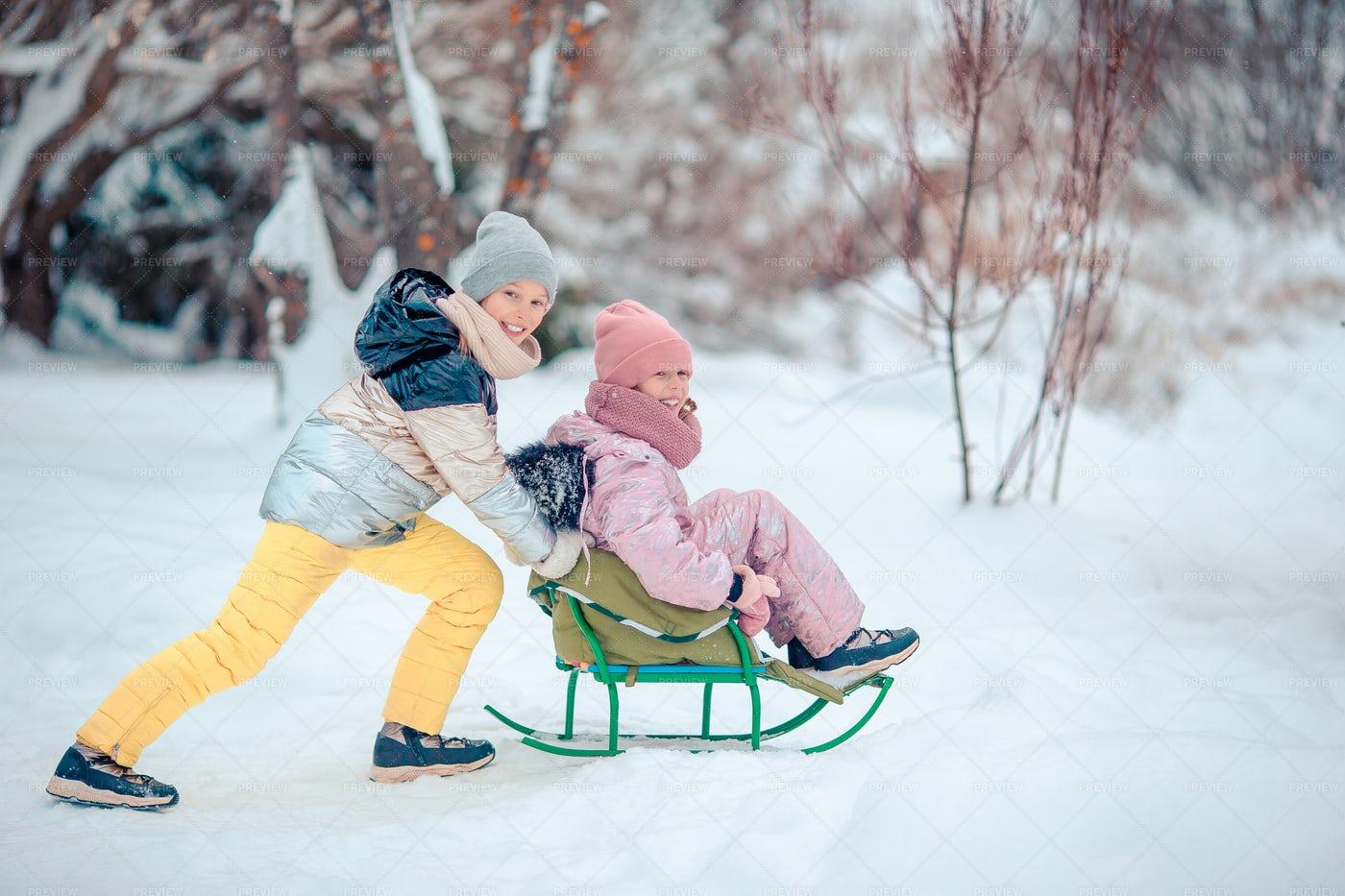 Happy Girls Sledding: Stock Photos