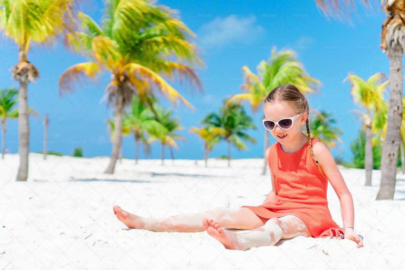 Little Girl Sitting At The Beach: Stock Photos