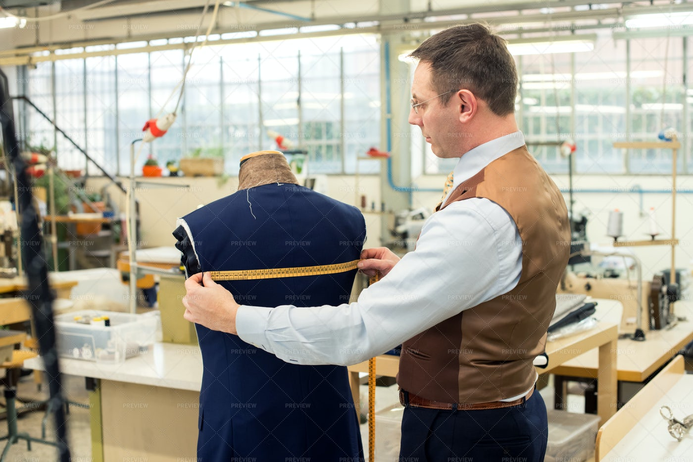 Tailor Measuring Jacket In His Workshop: Stock Photos