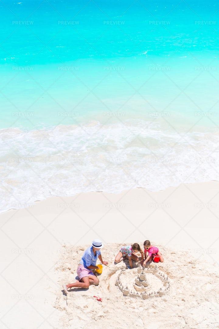 Family Making Sand Castle: Stock Photos