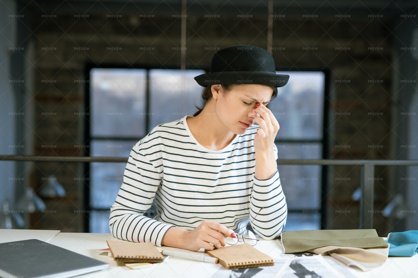 Tired Young Female Designer In Hat...: Stock Photos