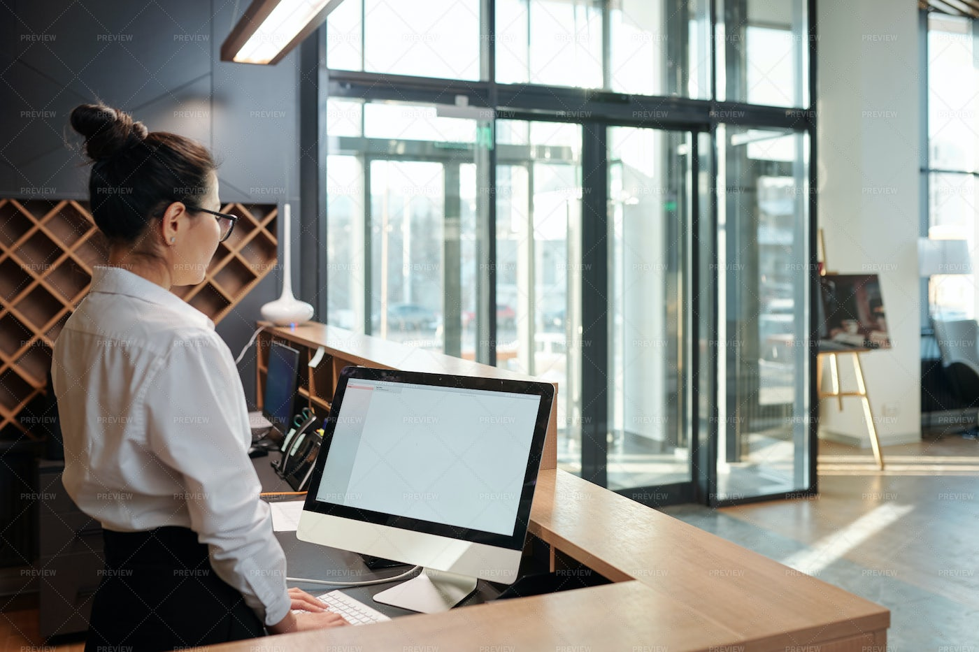 Young Female Receptionist Standing...: Stock Photos