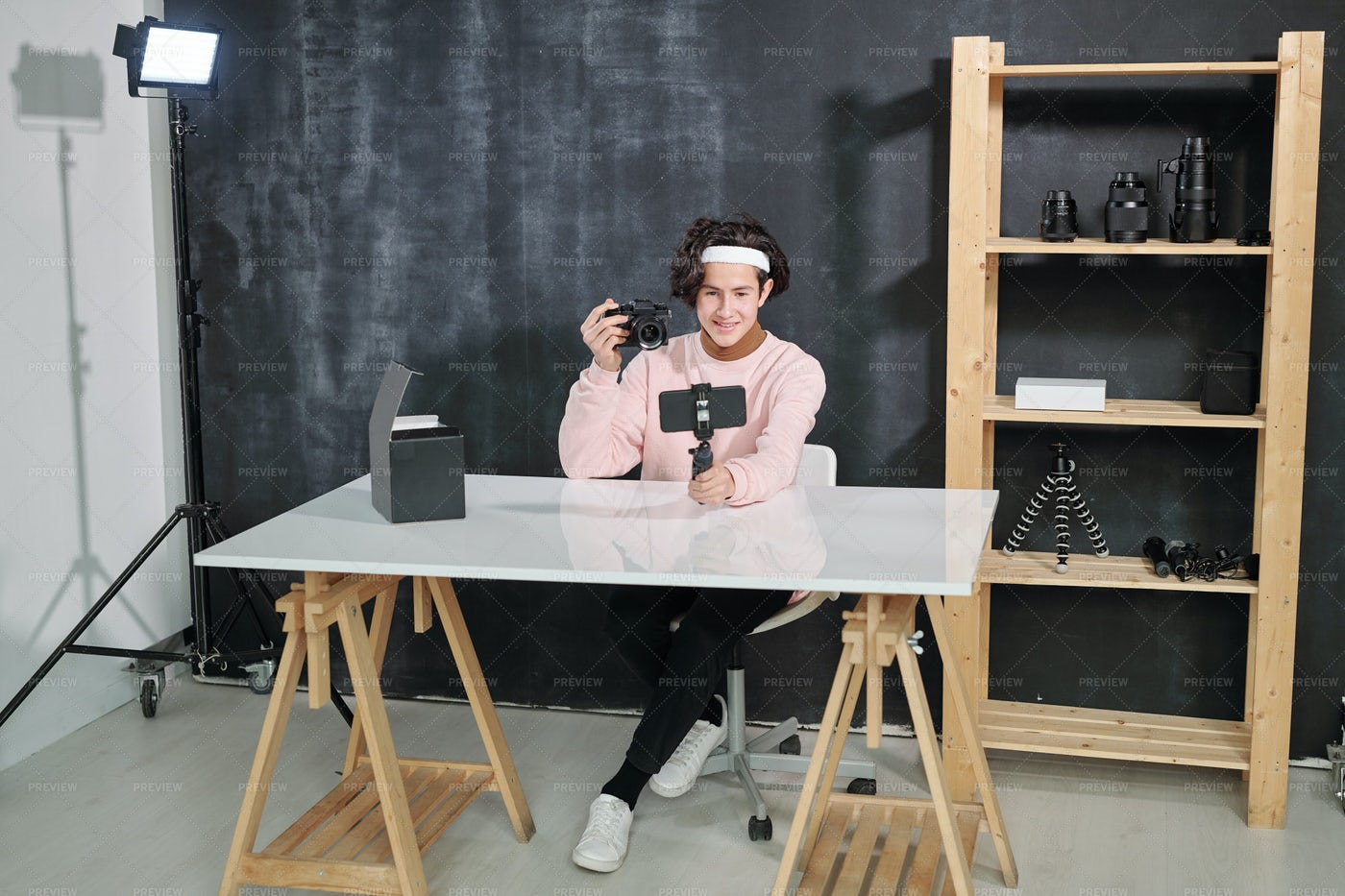 Male Vlogger Sitting By Desk And...: Stock Photos