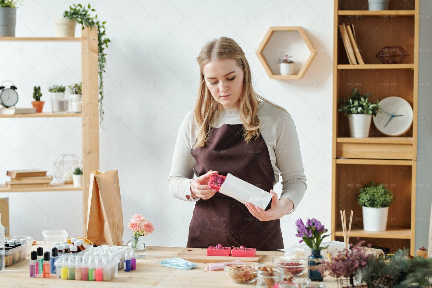 Blonde Female In Apron Putting...: Stock Photos
