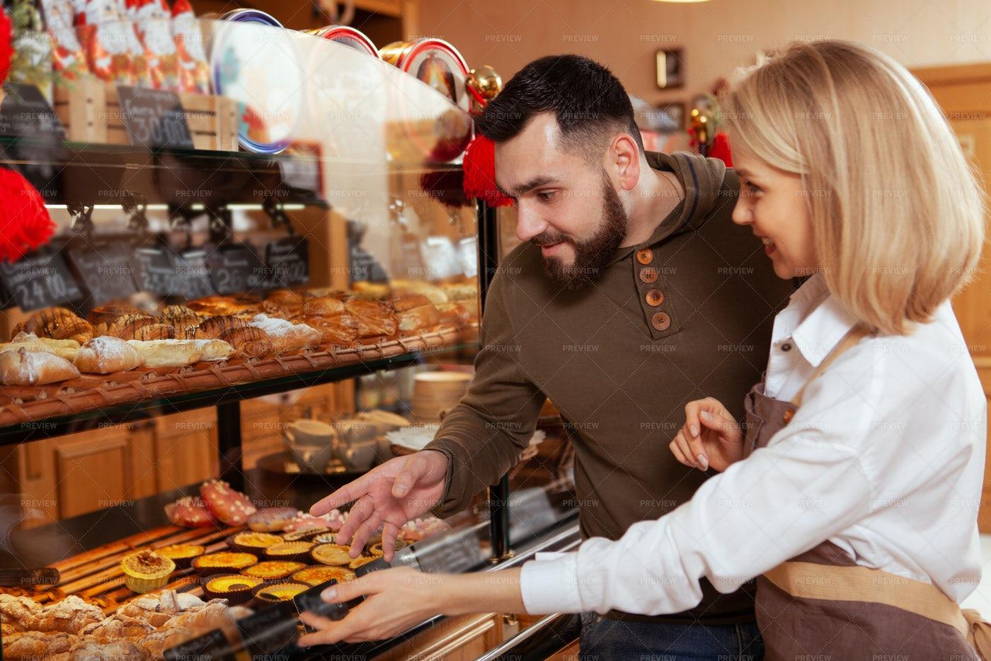 Baker Assists Customer: Stock Photos