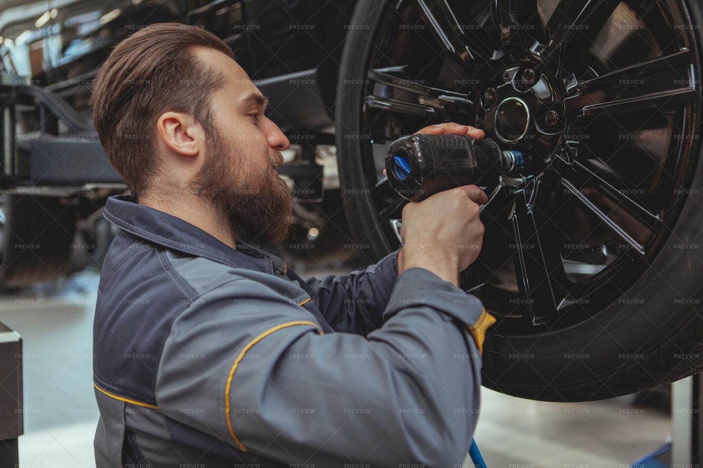 Mechanic Fixing Car Wheel: Stock Photos