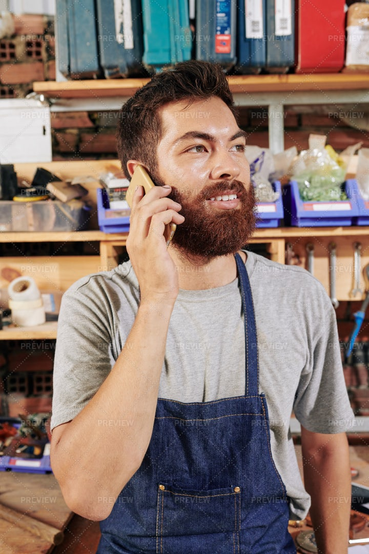 Carpenter Calling On Phone With Client: Stock Photos
