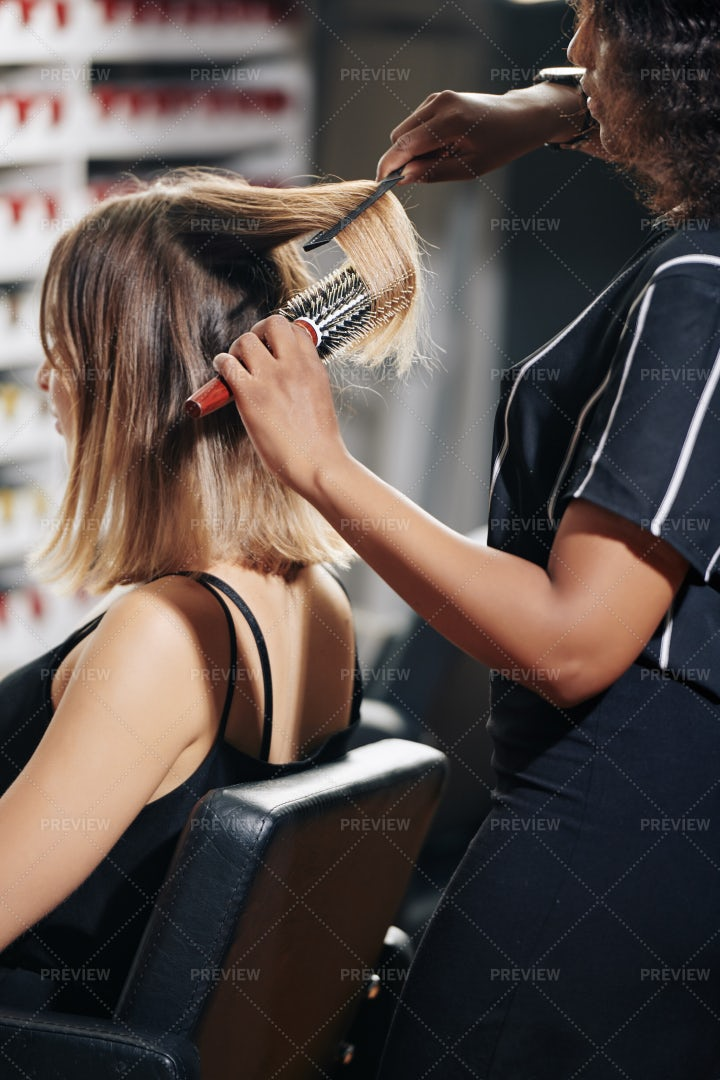 Stylist Brushing Hair Of Client: Stock Photos
