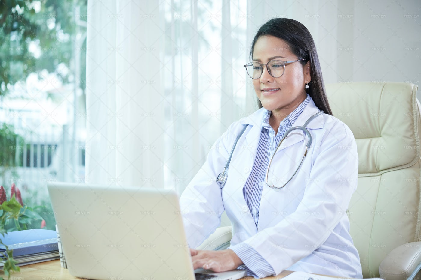 Smiling Doctor Working On Laptop: Stock Photos
