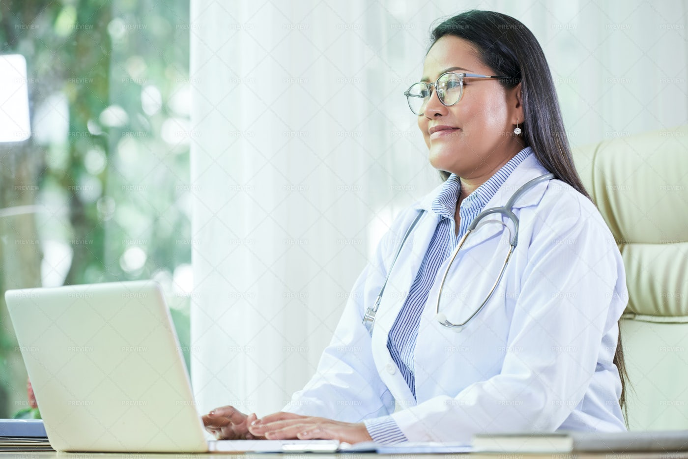 Positive Doctor Working On Laptop: Stock Photos