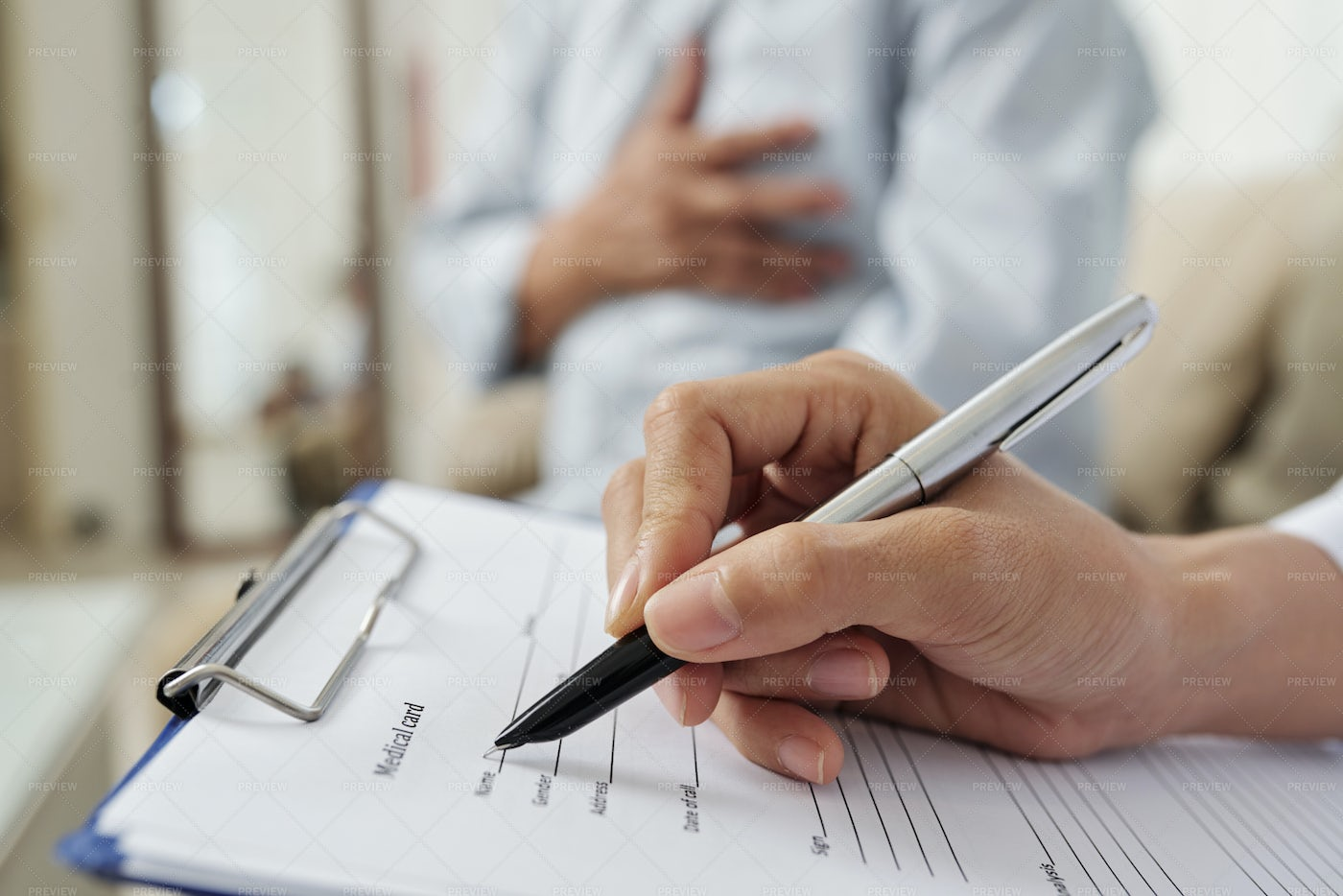 Doctor Filling The Medical Card: Stock Photos
