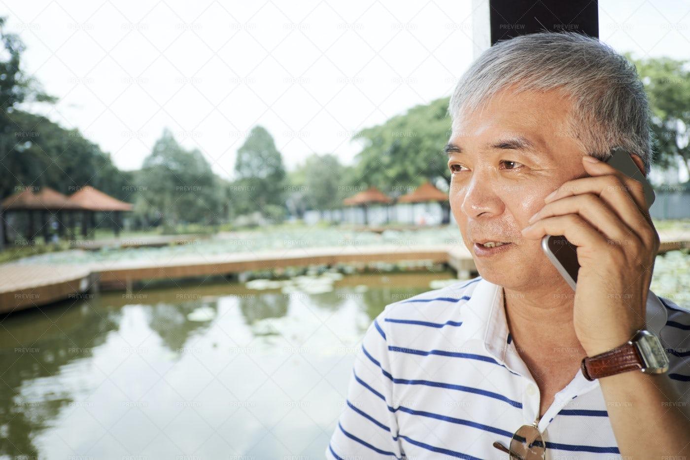 Asian Man Talking On Mobile Phone: Stock Photos