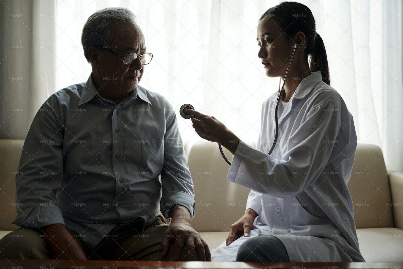 Doctor Examining Patient At Home: Stock Photos