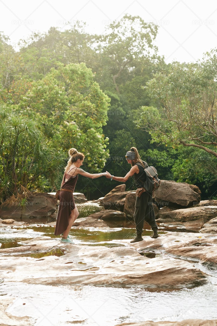 Couple Crossing Small River: Stock Photos