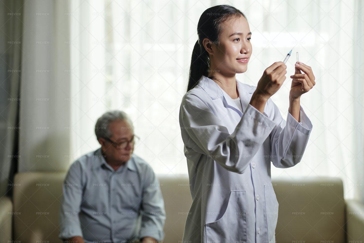 Doctor Preparing Vaccine For Senior Man: Stock Photos