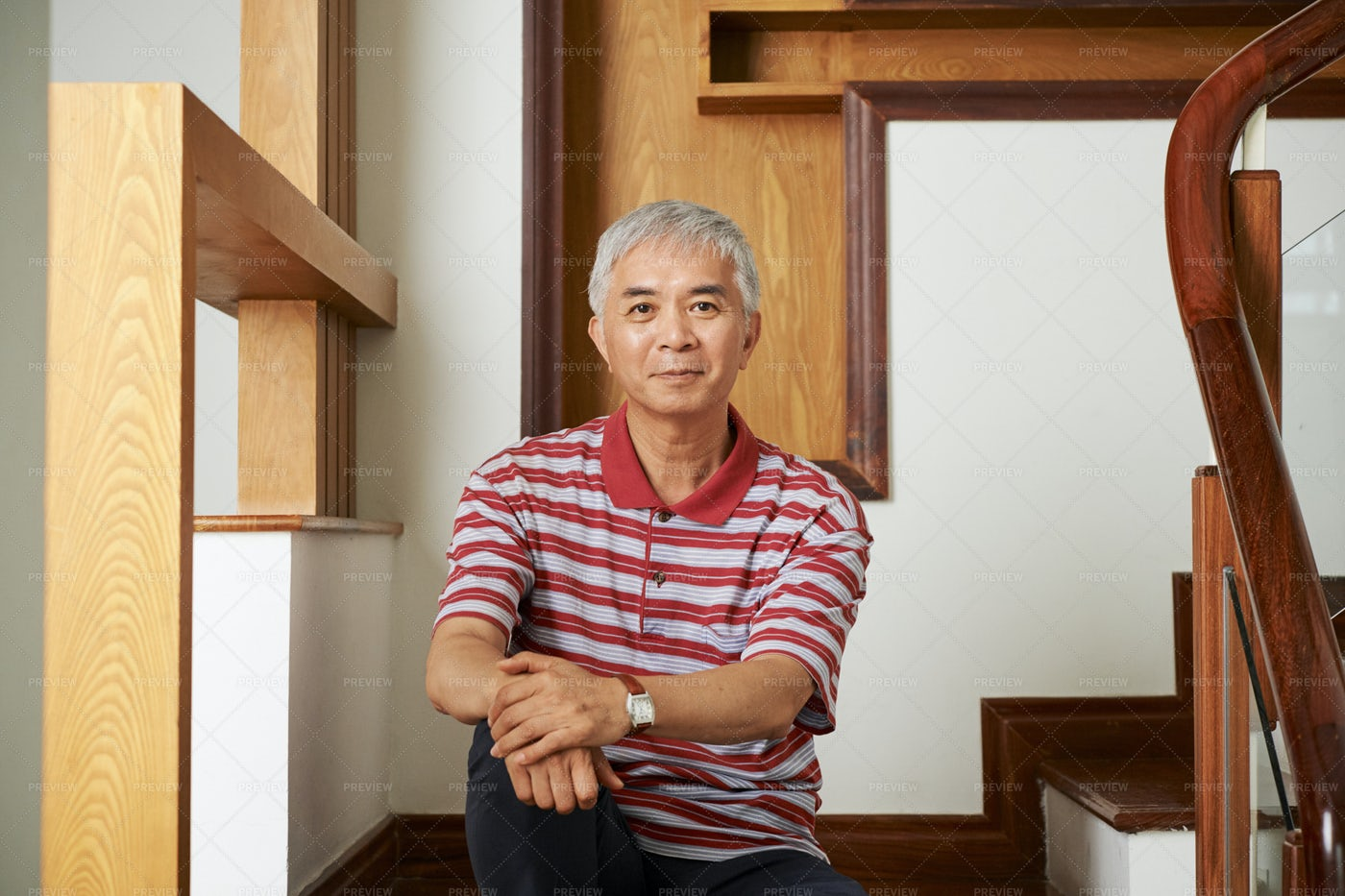 Asian Man Sitting On Staircase At Home: Stock Photos