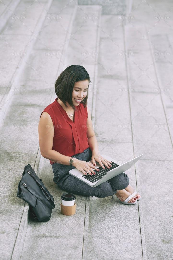 Woman Typing On Laptop Outdoors: Stock Photos