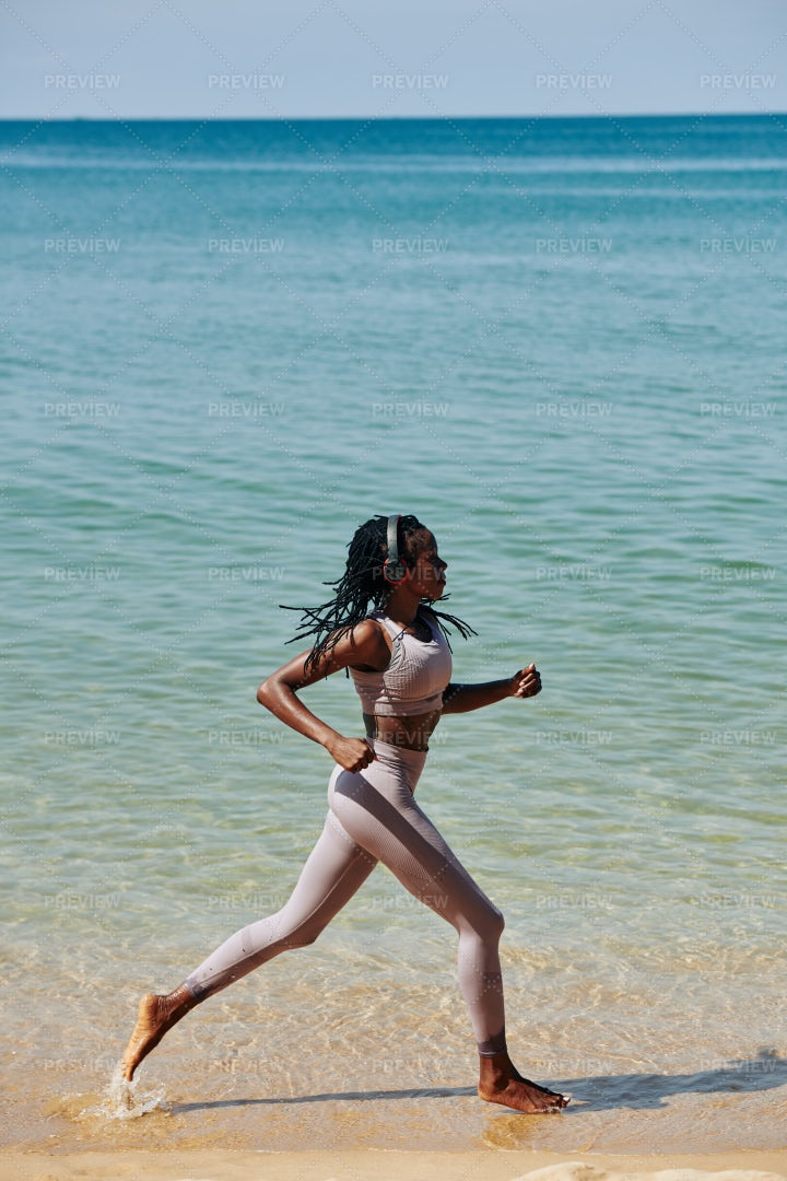 Young Woman Running Along The Beach: Stock Photos