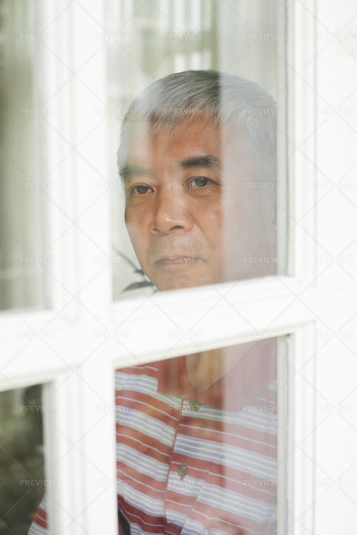 Asian Man Looking At Window: Stock Photos