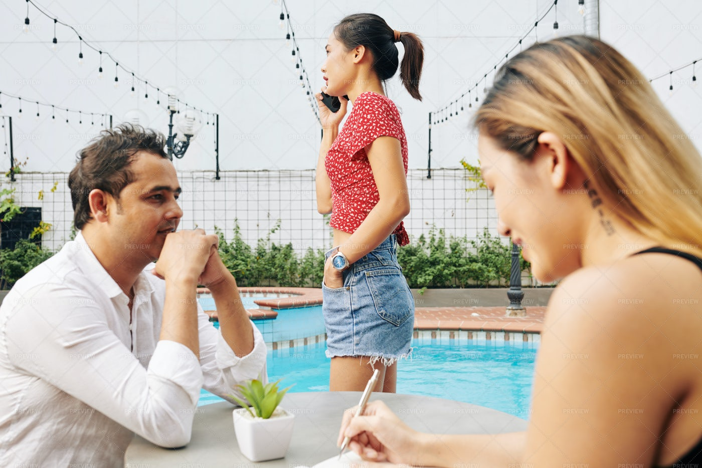 Digital Nomads Working By Swimming Pool: Stock Photos