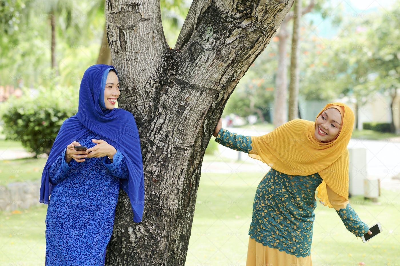 Cheerful Islamic Women Playing In Park: Stock Photos