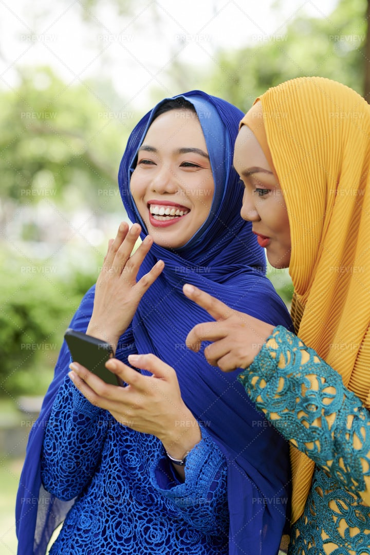 Laughing Muslim Women With Smartphone: Stock Photos