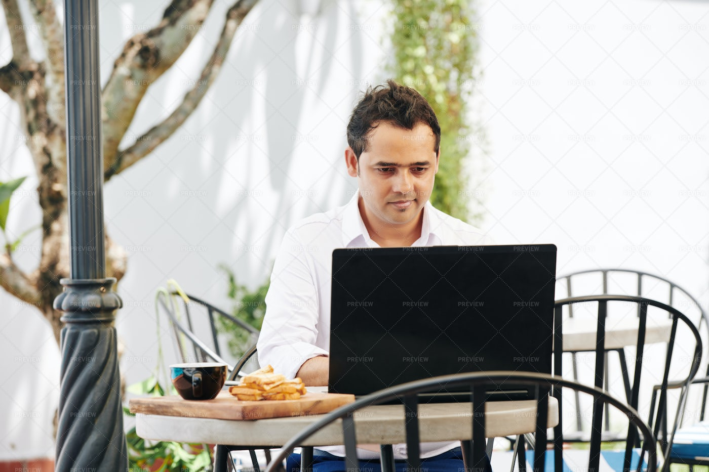 Indian Man Working On Laptop In Cafe: Stock Photos