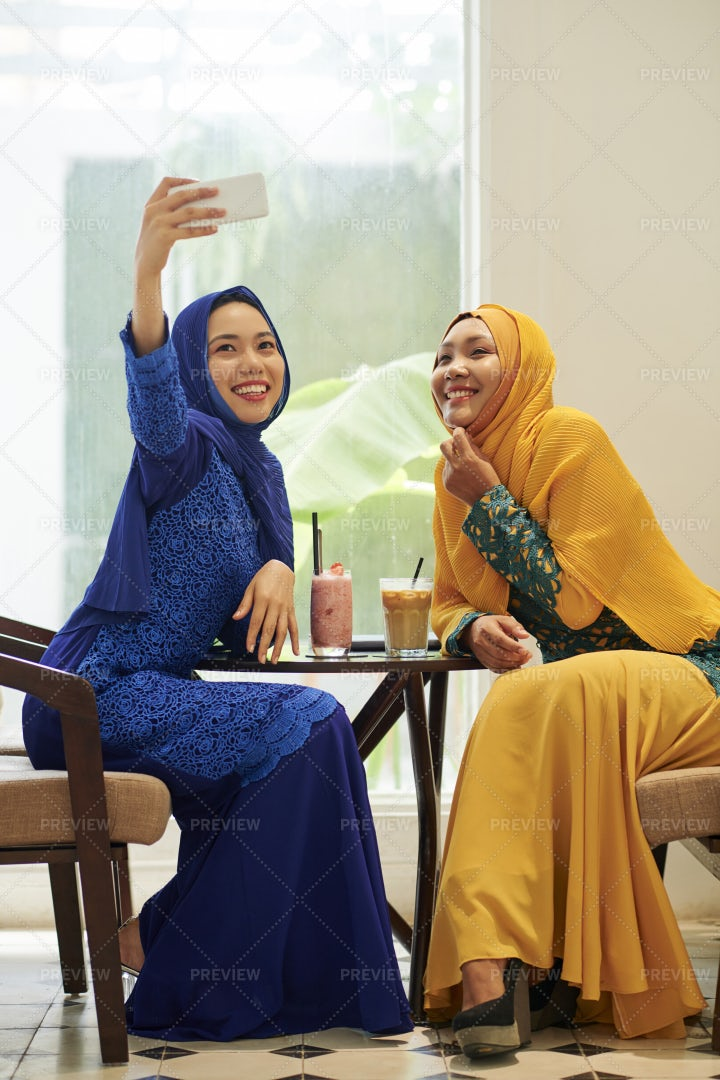 Muslim Women Photographing In Cafe: Stock Photos