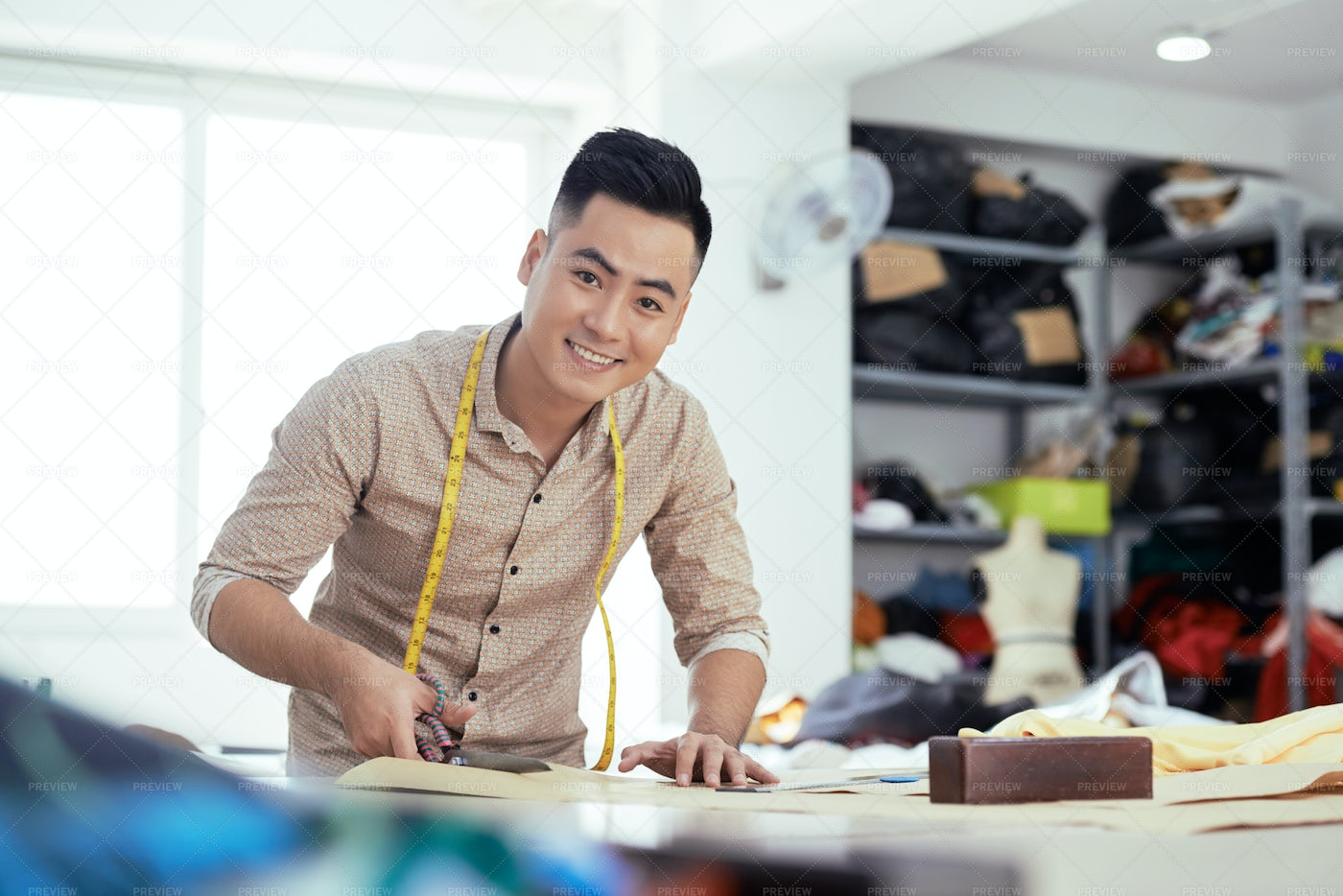 Cheerful Tailor Working On New Model: Stock Photos