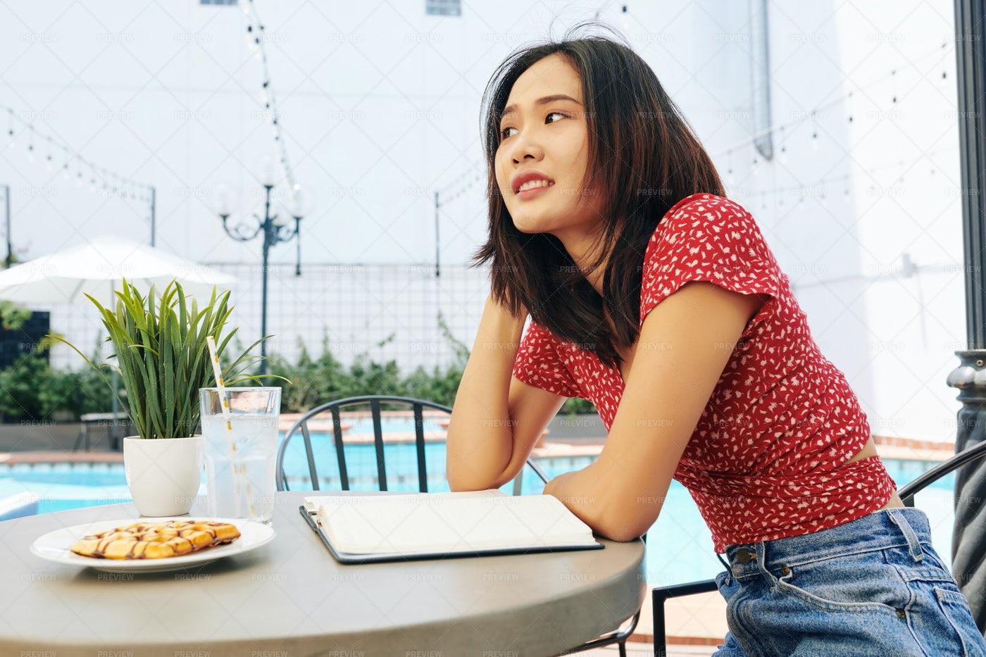 Pensive Asian Woman Sitting At Cafe: Stock Photos