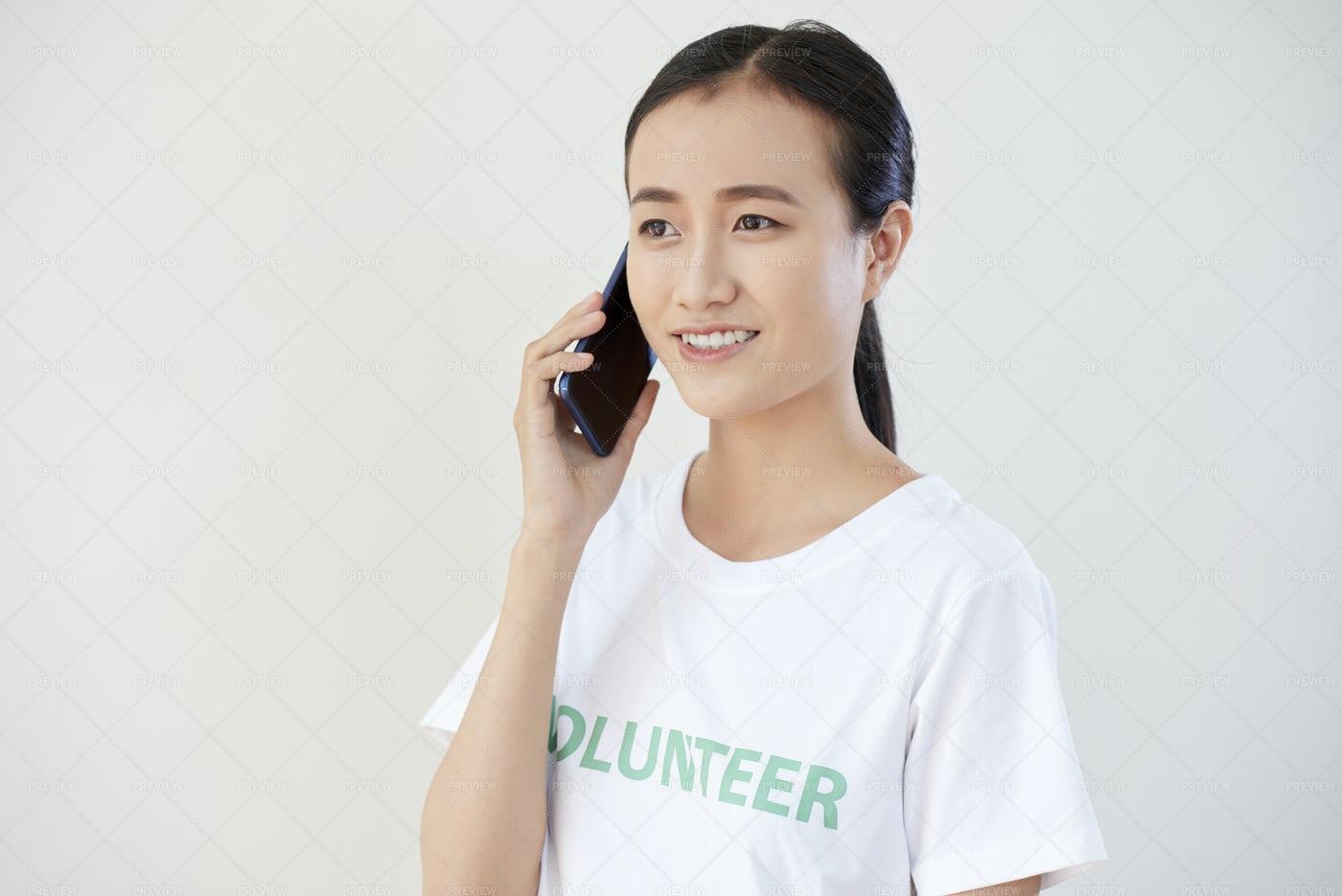 Volunteer Talking On Mobile Phone: Stock Photos