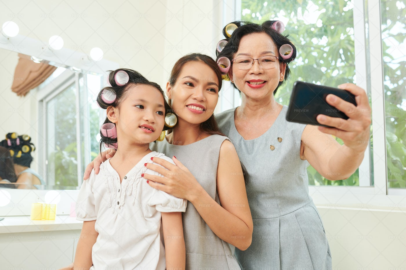 Asian Family With Curlers Making Selfie: Stock Photos