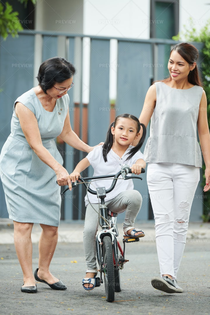 Girl Learning To Ride On Bicycle: Stock Photos