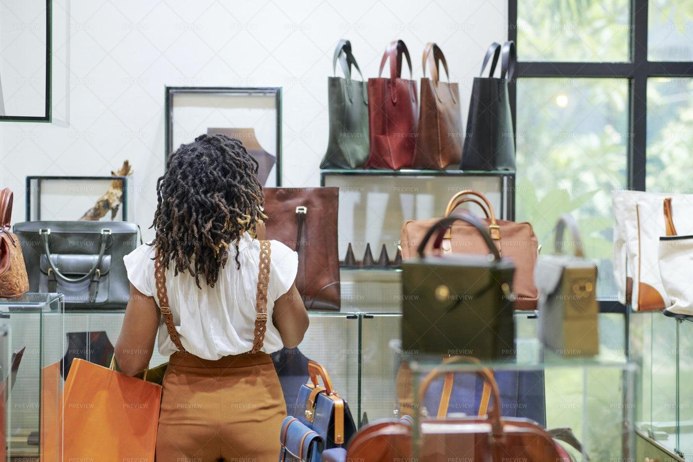 Woman Looking At Bag On Shelves: Stock Photos