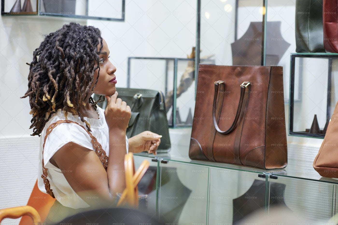 Doubting Woman Looking At Leather Bag: Stock Photos
