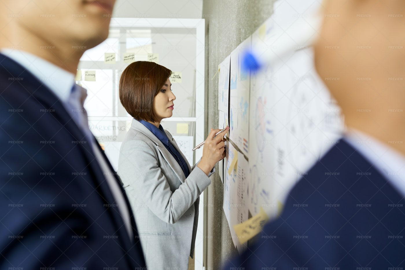 Businesswoman Checking Charts On Wall: Stock Photos