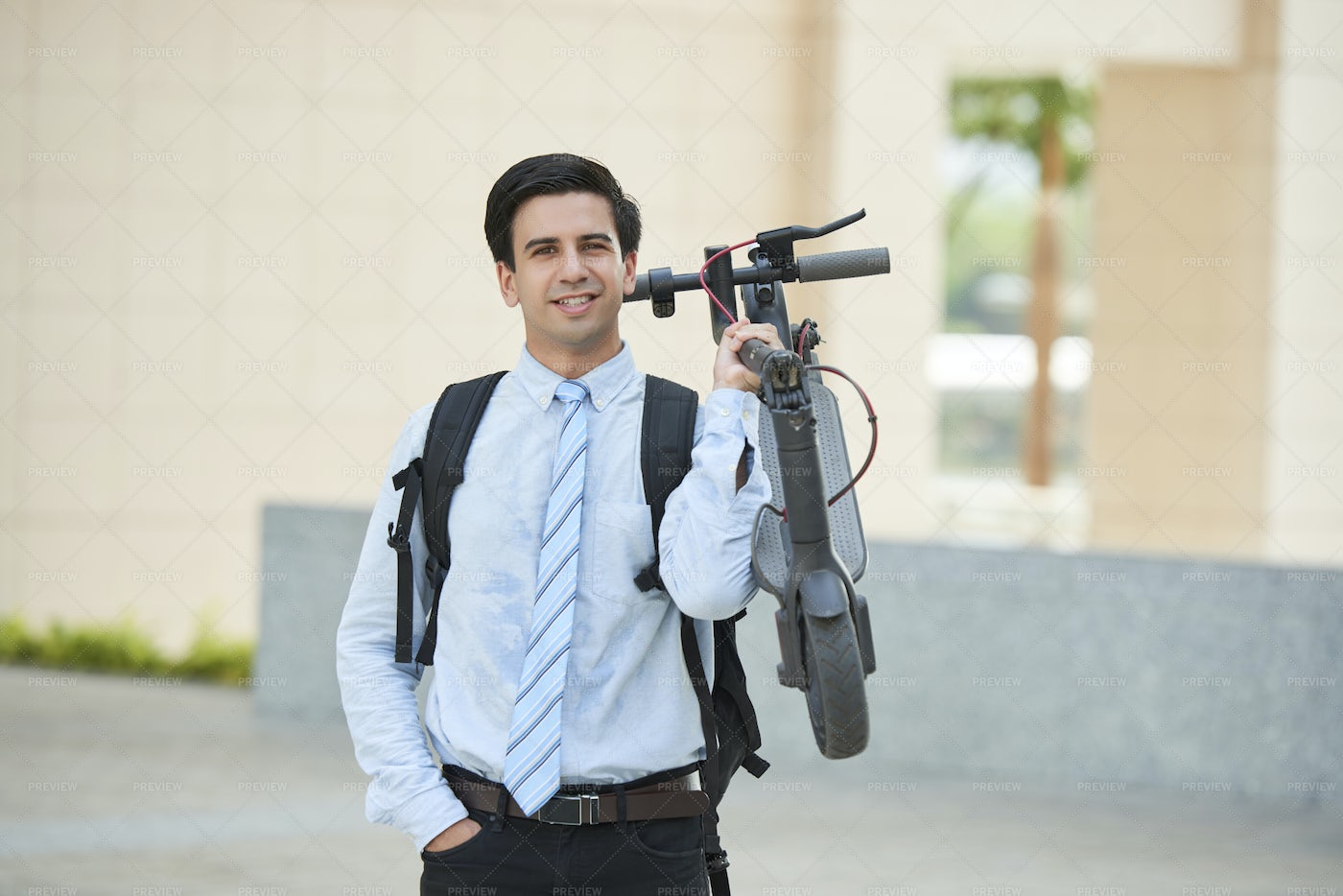 Office Worker Holding Scooter Outdoors: Stock Photos