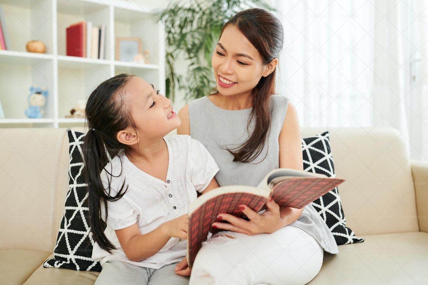 Family Reading A Book At Home: Stock Photos