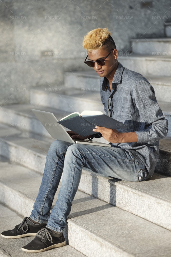 Black Man Reading Notes In His Planner: Stock Photos
