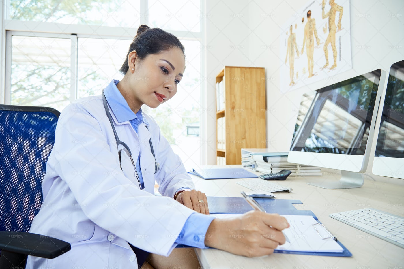 Female Doctor Writing A Prescription: Stock Photos