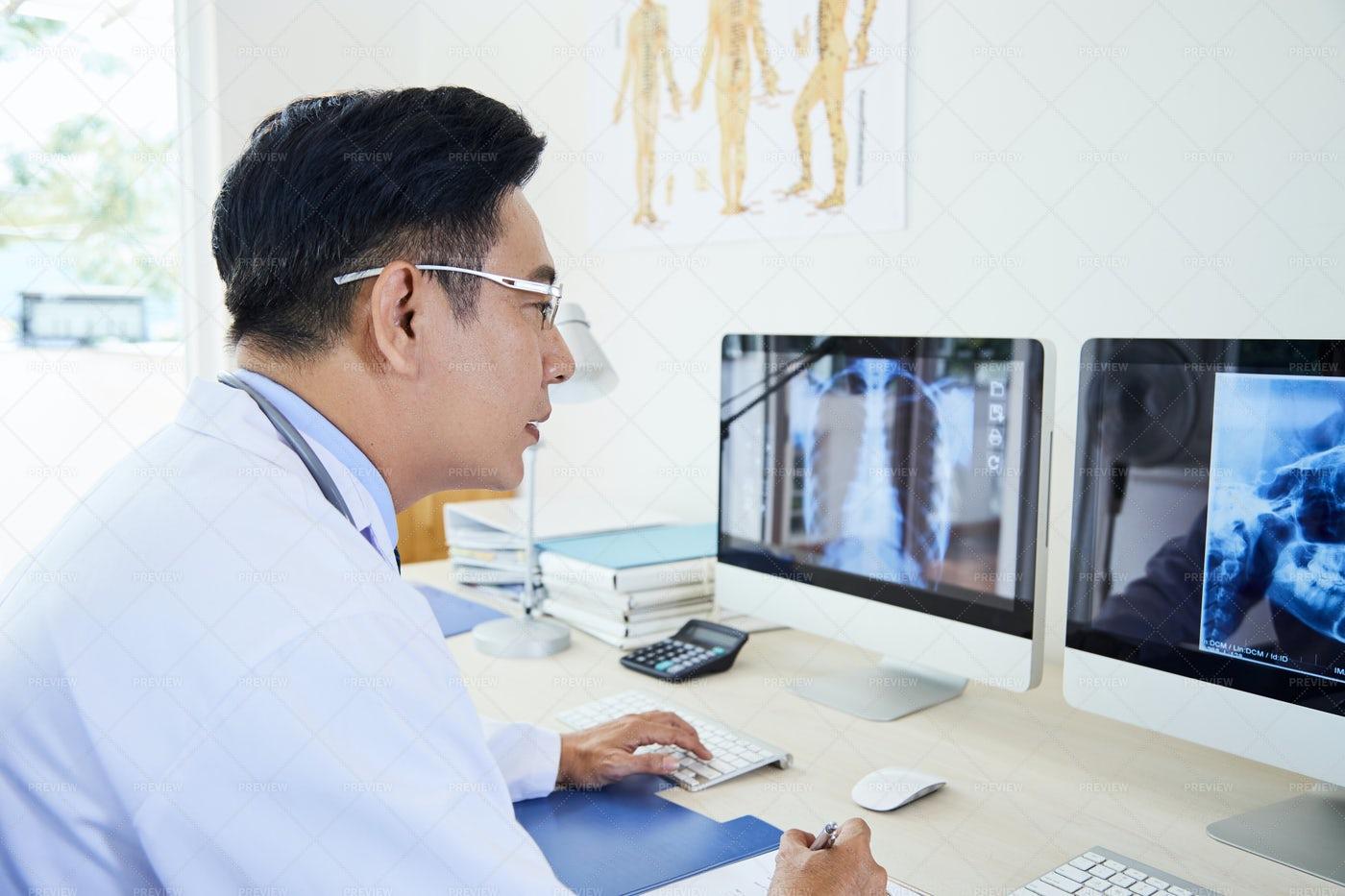 Mature Doctor Examining X-ray Image: Stock Photos
