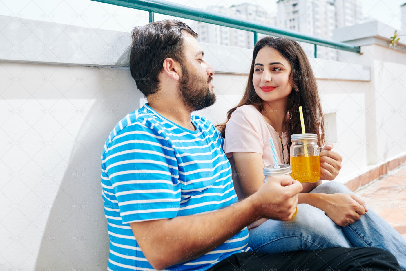 Couple Resting On Rooftop With Cocktail: Stock Photos