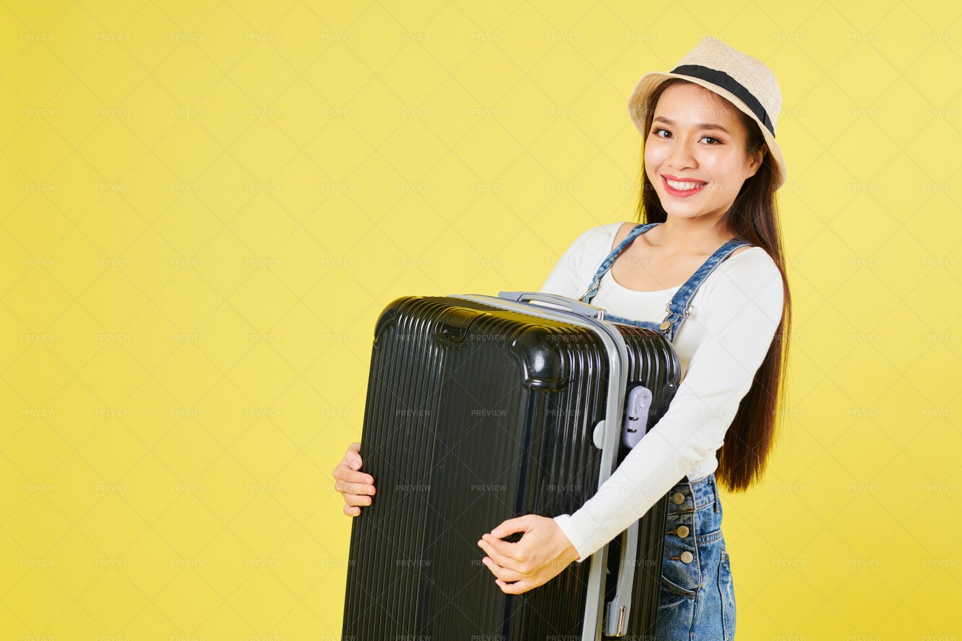 Female Tourist Lifting Heavy Suitcase: Stock Photos