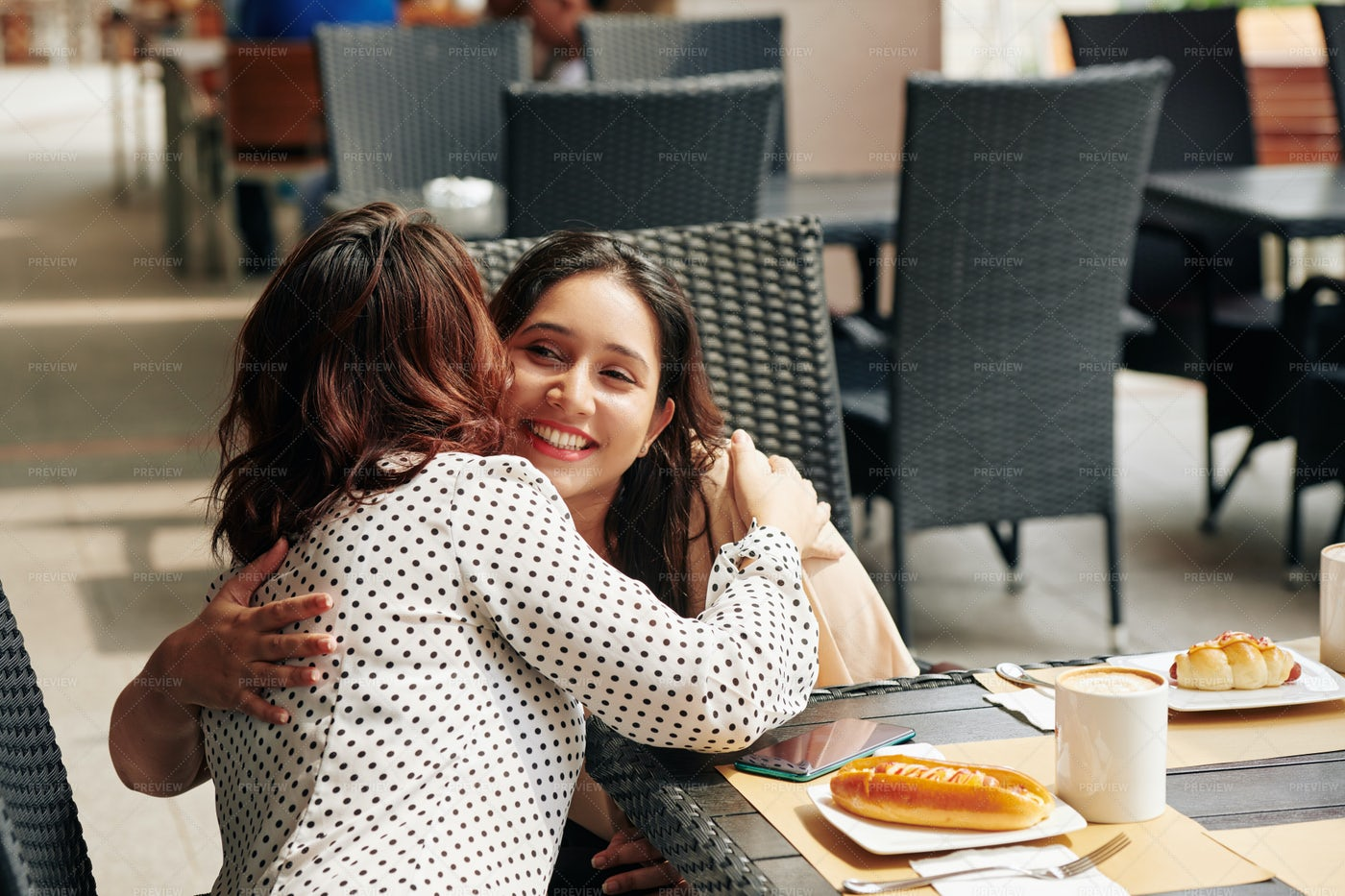 Firends Hugging At Cafe Table: Stock Photos